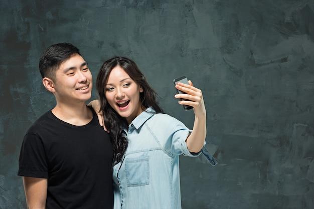Ritratto delle coppie coreane sorridenti su una parete grigia