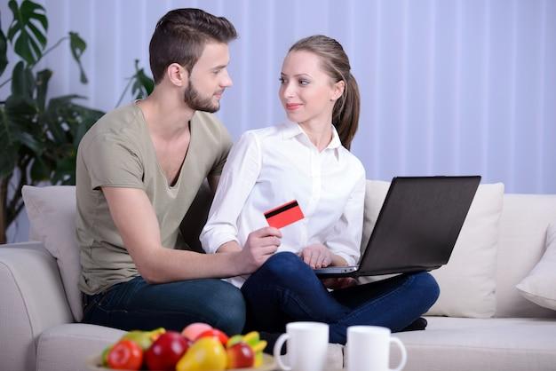 Ritratto delle coppie felici che comperano online.