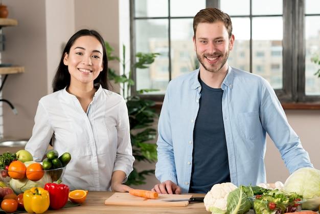 Ritratto delle coppie felici che stanno dietro il contatore di cucina con differenti tipi di verdure