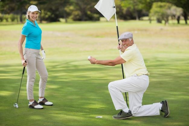 Ritratto delle coppie mentre palla da golf della tenuta dell'uomo