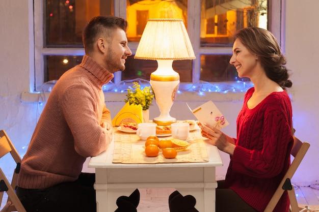 Ritratto delle coppie romantiche alla cena di san valentino con il regalo