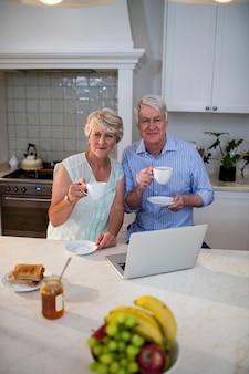 Ritratto delle coppie senior che mangiano tè in cucina