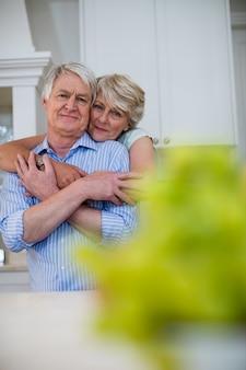 Ritratto delle coppie senior che si abbracciano in cucina