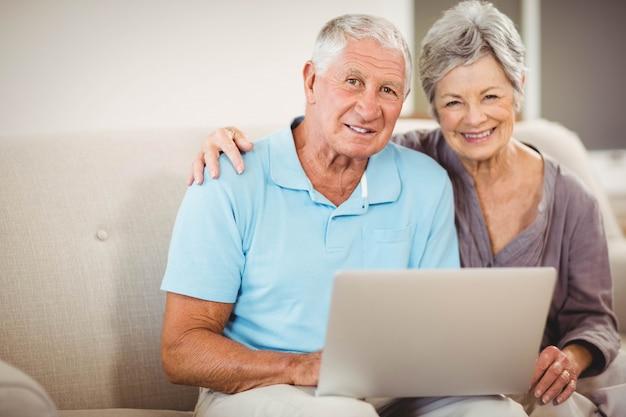 Ritratto delle coppie senior che si siedono sul sofà e che sorridono nel salone