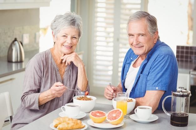 Ritratto delle coppie senior sorridenti che mangiano prima colazione