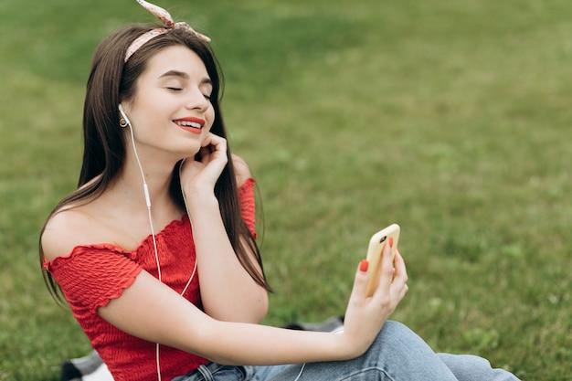 Ritratto delle cuffie d'uso della giovane bella donna contenta, ascoltando musica con gli occhi chiusi e trovantesi sull'erba in parco