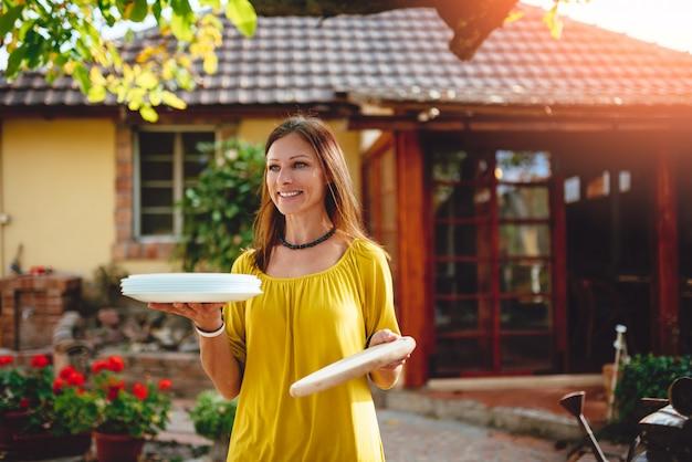 Ritratto delle donne che tengono i piatti nel patio del cortile