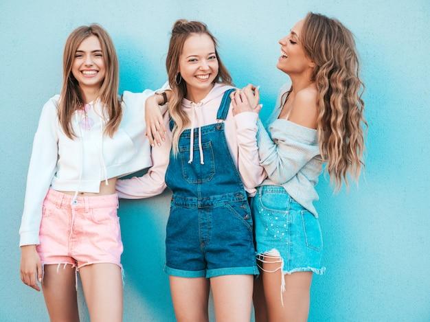 Ritratto delle donne sexy che posano nella via vicino alla parete blu divertiresi dei modelli positivi