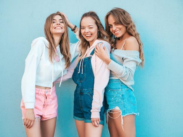 Ritratto delle donne sexy che posano nella via vicino alla parete blu modelli divertenti divertendosi mostrano la lingua
