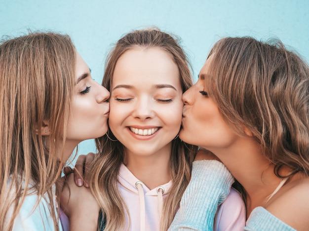 Ritratto delle donne spensierate sexy che posano nella via. modelli positivi che baciano il loro amico in guancia