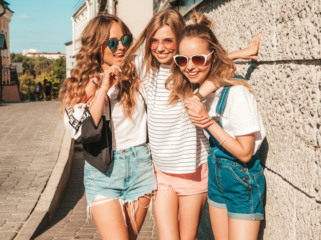 Ritratto delle donne spensierate sexy che posano nella via vicino alla parete modelli positivi divertendosi in occhiali da sole abbracciare
