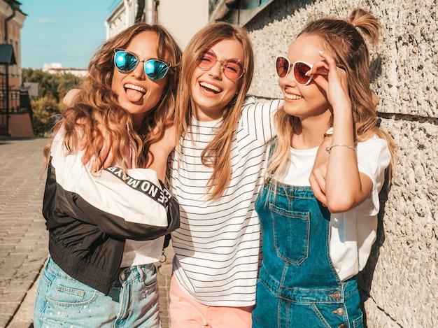 Ritratto delle donne spensierate sexy che posano sui precedenti della via modelli positivi divertendosi in occhiali da sole abbracciare