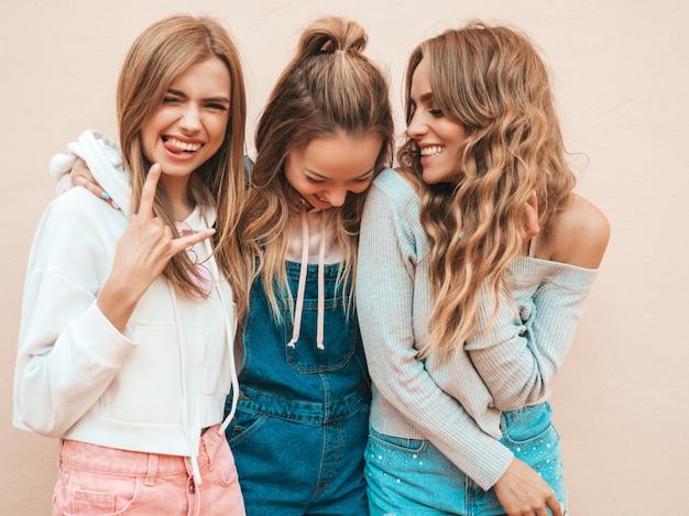 Ritratto delle donne spensierate sexy che posano sulla via vicino alla parete divertiresi dei modelli positivi abbracciare