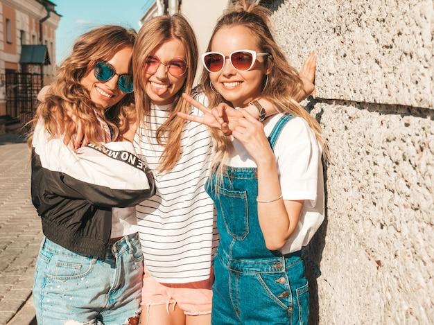 Ritratto delle donne spensierate sexy che posano vicino alla parete nella via. modelli positivi divertendosi in occhiali da sole