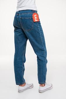 Ritratto delle gambe di una femmina in jeans