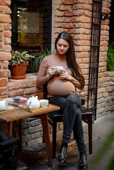 Ritratto delle giovani free lance della donna incinta che utilizza computer portatile per il lavoro a distanza mentre sedendosi nel caffè moderno con la tazza di tè