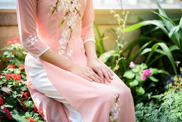 Ritratto delle ragazze asiatiche con il costume tradizionale del vestito di ao-dai vietnam che si siede nel giardino floreale