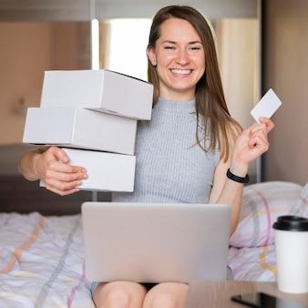 Ritratto delle scatole della spesa felici della tenuta della donna