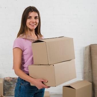 Ritratto delle scatole di cartone sorridenti della tenuta della giovane donna a disposizione che guardano alla macchina fotografica