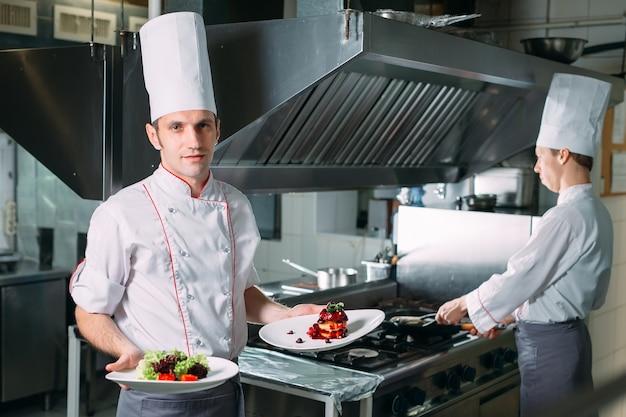 Ritratto dello chef nella cucina del ristorante con un piatto pronto foie gras.