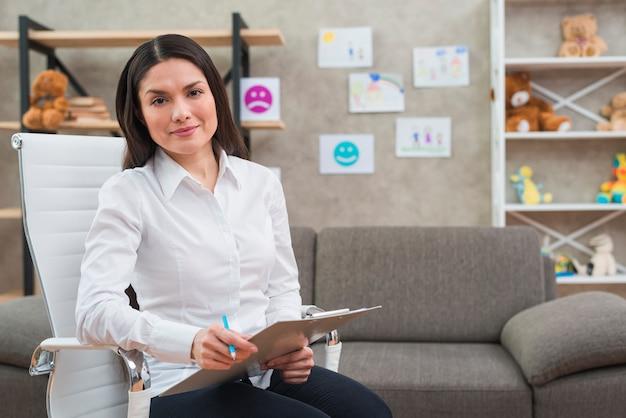 Ritratto dello psicologo femminile sorridente che si siede sulla sedia bianca con la lavagna per appunti e la matita nel suo ufficio
