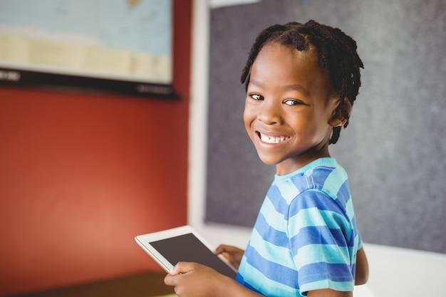 Ritratto dello scolaro che tiene compressa digitale in aula