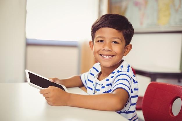 Ritratto dello scolaro che utilizza compressa digitale nell'aula