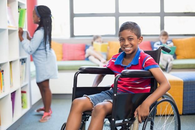 Ritratto dello scolaro disabile sulla sedia a rotelle in biblioteca