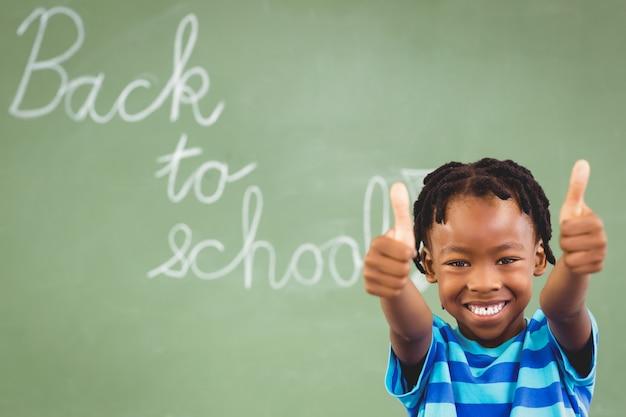 Ritratto dello scolaro sorridente che mostra i pollici su nell'aula