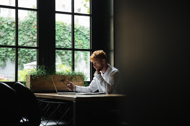 Ritratto dello smartphone barbuto della tenuta dell'uomo di affari della testarossa seria, sedentesi nel luogo di lavoro