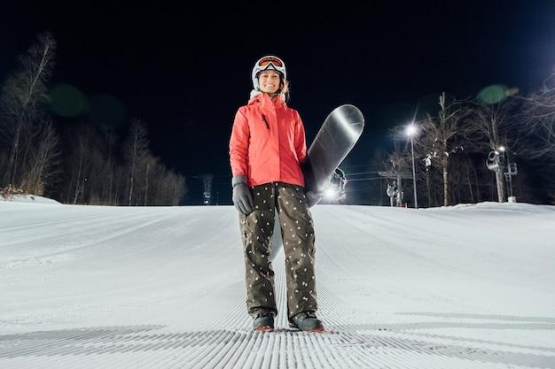 Ritratto dello snowboarder femminile al pendio di sera. concetto di sport invernali