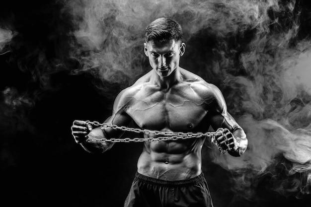 Ritratto dello sportivo muscolare che strappa la catena del metallo