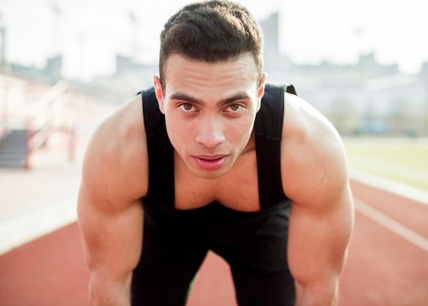 Ritratto dello sportivo muscolare sicuro che esamina macchina fotografica