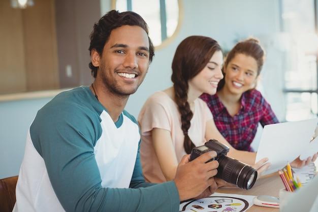 Ritratto dello stilista che tiene macchina fotografica digitale con i colleghi