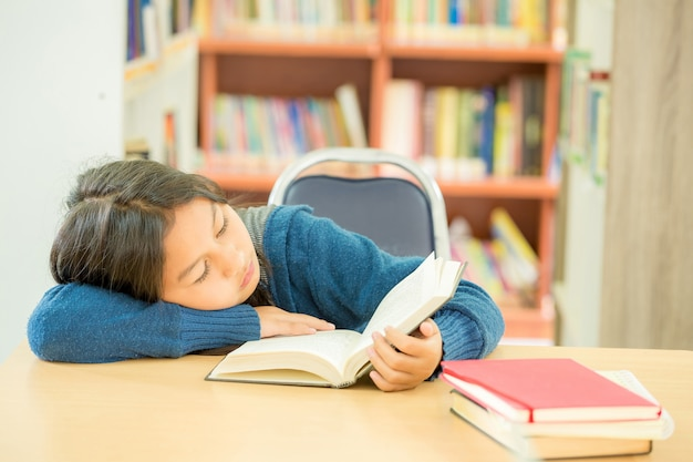 Ritratto dello studente abile con il libro aperto che lo legge nella biblioteca di istituto universitario