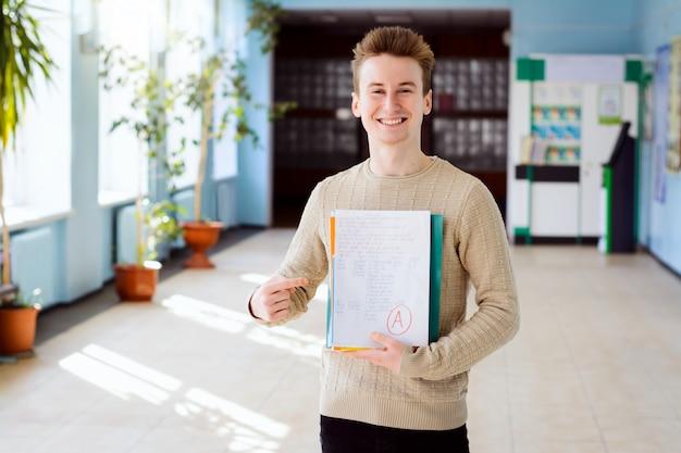 Ritratto dello studente di college maschio che sorride alla macchina fotografica e che indica i materiali di apprendimento