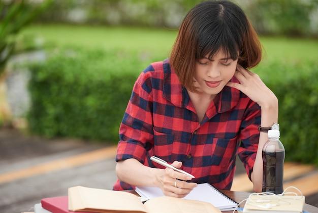 Ritratto dello studente occupato con i compiti in città universitaria all'aperto