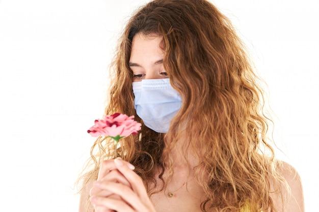 Ritratto dello studio di giovane donna che indossa una maschera di protezione medica
