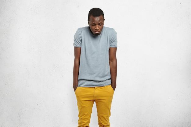 Ritratto dello studio di giovane maschio africano che scrolla le spalle le spalle e che guarda giù con l'espressione confusa colpevole