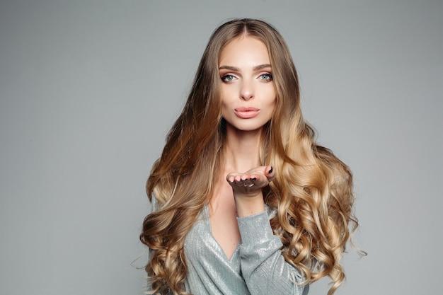 Ritratto dello studio di una donna bionda attraente con capelli spessi lunghi