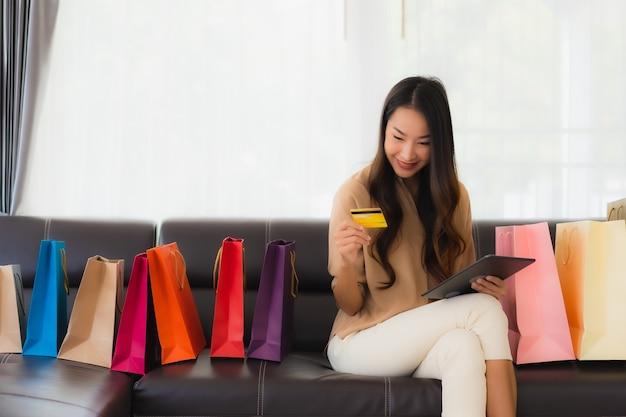 Ritratto di acquisto online della bella giovane donna asiatica con la carta di credito e lo smartphone intorno ai sacchetti della spesa
