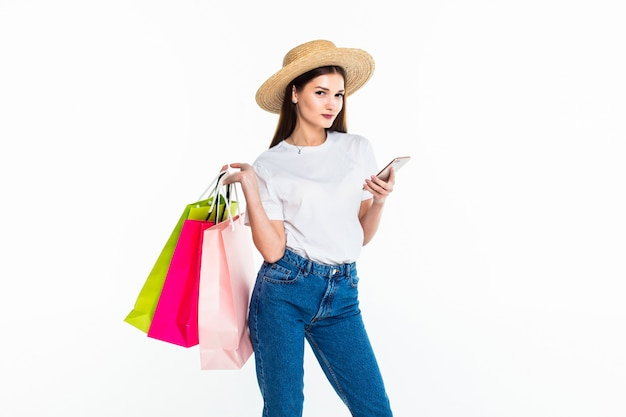 Ritratto di acquisto splendido della donna facendo uso del suo smartphone isolato sulla parete bianca