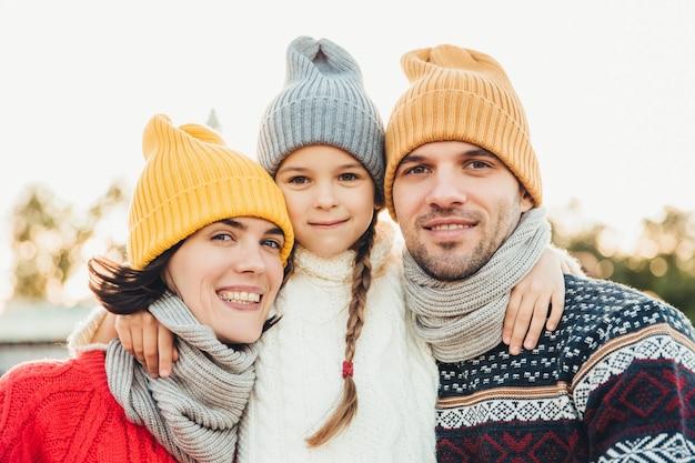 Ritratto di adorabile bambina indossa cappello lavorato a maglia e maglione si trova tra i genitori, abbracciarli