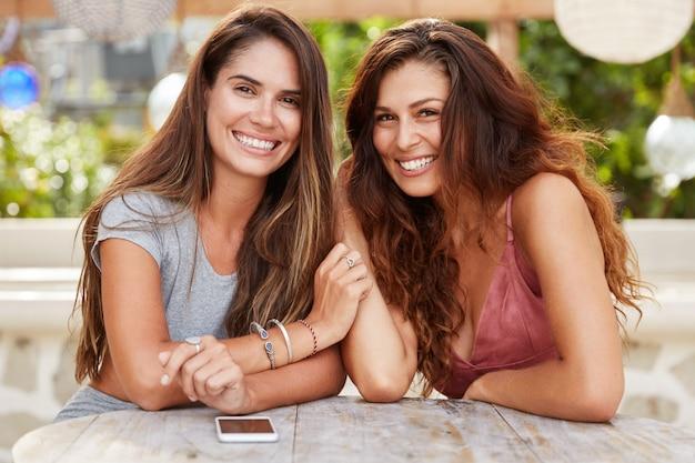 Ritratto di adorabile donna bruna si incontrano nella caffetteria, circondato da smart phone, hanno un aspetto attraente