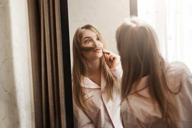 Ritratto di adorabile giocosa donna bionda che fa i baffi da ciocca di capelli, guardando nello specchio e facendo una faccia buffa