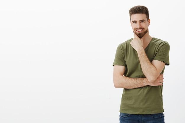 Ritratto di affascinante charismasitc uomo barbuto caucasico con gli occhi azzurri strofinando il mento come sorridendo felice in posa sul lato destro della copia spazio sopra il muro bianco, udendo un'idea eccellente
