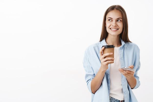Ritratto di affascinante dipendente di sesso femminile di bell'aspetto intelligente ed elegante che tiene la tazza di carta della bevanda e dello smartphone che guarda a sinistra con il sorriso soddisfatto che ha piano