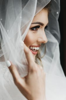 Ritratto di affascinante sposa avvolta in un velo