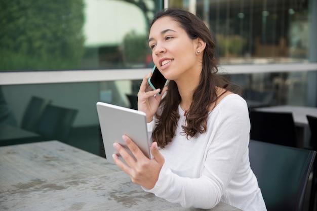 Ritratto di allegra giovane imprenditrice parlando sul telefono cellulare