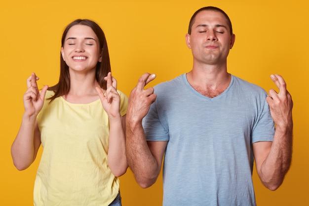 Ritratto di allegre coppie energiche in piedi l'una accanto all'altra, incrociando le dita, alzando le braccia, chiudendo le mani, esprimendo desideri, pensando a cose positive, pregando. concetto di famiglia.